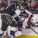 Los Angeles Kings defenseman Jake Muzzin (6) and Phoenix Coyotes forward Jeff Halpern (14) vie for the puck during the first period of an NHL hockey game, Wednesday, April 2, 2014, in Los Angeles The Associated Press
