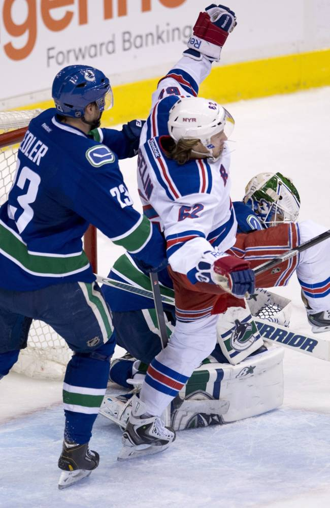 Vancouver Canucks defenseman Alexander Edler (23) tries to clear New York Rangers left wing Carl Hagelin (62) from in front of Canucks goalie Eddie Lack during the second period of an NHL hockey game Tuesday, April 1, 2014, in Vancouver, British Columbia
