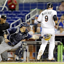 San Diego Padres catcher Yasmani Grandal, center, is unable to tag Miami Marlins' Casey McGehee (9) who scores on a double by Garrett Jones during the fifth inning of a baseball game on Friday, April 4, 2014, in Miami The Associated Press