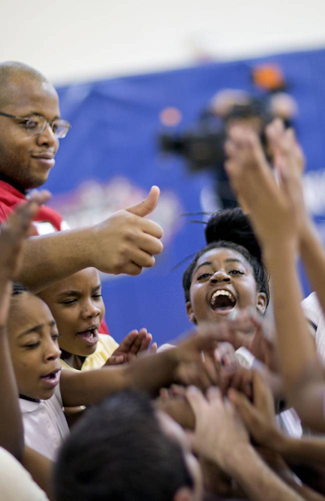 Students from M. Agnes Jones Elementary School join Atlanta Falcons' Harland Gunn, left, in a cheer as the NFL football team takes part in the volunteer project,