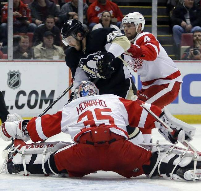 Detroit Red Wings goalie Jimmy Howard (35) stops a shot by Pittsburgh Penguins' Deryk Engelland (46) as Red Wings' Jakub Kindl (4) helps defend the goal during the first period of an NHL hockey game Thursday, March 20, 2014 in Detroit