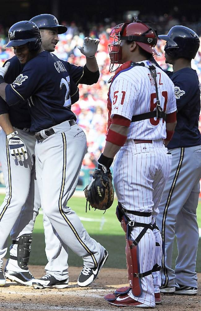 Philadelphia Phillies' catcher Carlos Ruiz (51) watches Milwaukee Brewers' Ryan Braun, left, celebrate with Carlos Gomez, middle, and Jean Segura, right, after hitting a three run homer in the third inning of an MLB National League baseball game on Tuesday, April 8, 2014, in Philadelphia