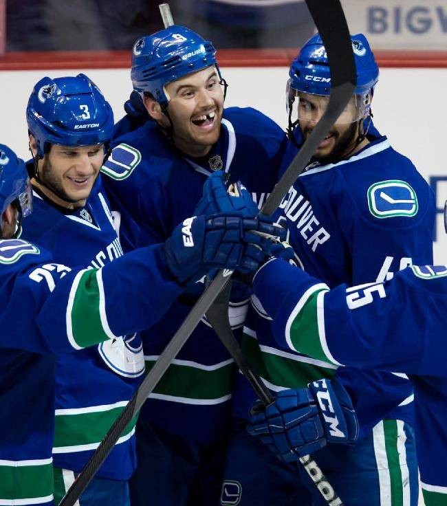 Vancouver Canucks', from left, Alexander Edler, of Sweden, Kevin Bieksa, Zack Kassian, Darren Archibald and Brad Richardson celebrate Kassian's goal against the Toronto Maple Leafs during the second period of an NHL hockey game in Vancouver, British Columbia, on Saturday, Nov. 2, 2013