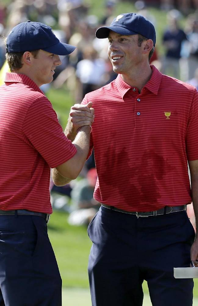 United States teammates Matt Kuchar, right, and Jordan Spieth shake hands following a practice round for the Presidents Cup golf tournament at Muirfield Village Golf Club Wednesday, Oct. 2, 2013, in Dublin, Ohio