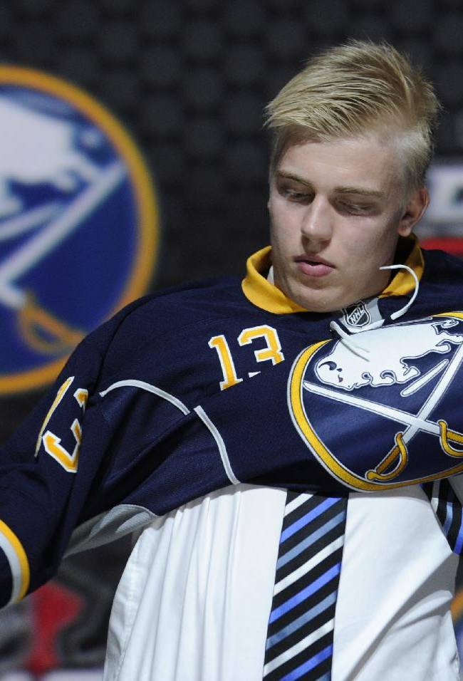 In this June 30, 2013 file photo, Rasmus Ristolainen, of Finland, pulls on a Buffalo Sabres jersey after being chosen 8th overall in the first round of the NHL hockey draft, in Newark, N.J. The Sabres have a few more decisions to make Monday, Sept. 30, 2013,  to set their roster before opening the season at Detroit on Wednesday. One thing is for certain, the Sabres lineup will include rookie 18-year-old defenseman Rasmus Ristolainen