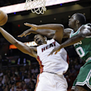 Miami Heat's Chris Bosh, left, attempts to shoot as Boston Celtics' Brandon Bass defends during the first half of an NBA basketball game Saturday, Nov. 9, 2013, in Miami The Associated Press