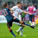 Bayern's Philipp Lahm, left, and Manchester City's James Milner, right, challenge for the ball during the Champions League group D soccer match between FC Bayern Munich and Manchester City, in Munich, southern Germany, Tuesday, Dec. 10, 2013
