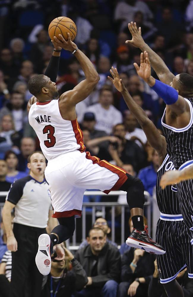 Miami Heat's Dwyane Wade (3) takes a shot over Orlando Magic defenders including Glen Davis, right, during the second half of an NBA basketball game in Orlando, Fla., Saturday, Jan. 4, 2014. Miami won the game 110-94