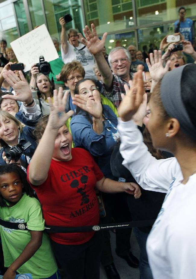 Minnesota Lynx's Maya Moore is welcomed by fans at the Humphrey Terminal, Friday, Oct. 11, 2013, in Bloomington, Minn. The Lynx won their second WNBA title in three years beating the Atlanta Dream 86-77 on Thursday