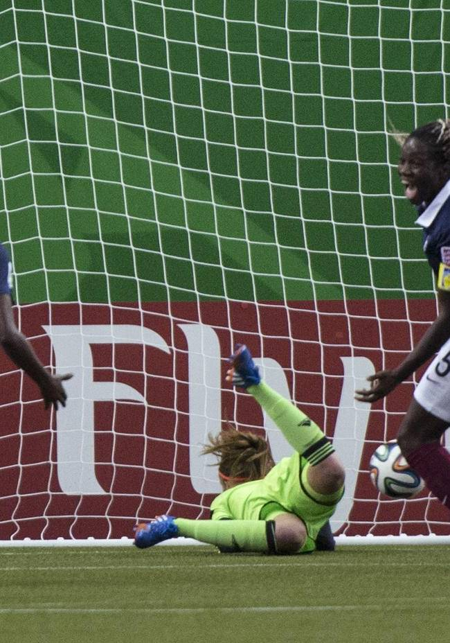 France's Griedge Mbock Bathy, right front, celebrates her goal past Germany goalkeeper Meike Kaemper as teammate Aissatou Tounkara, left, watches during the first half of a FIFA U-20 women's World Cup semifinal in Montreal on Wednesday, Aug. 20, 2014