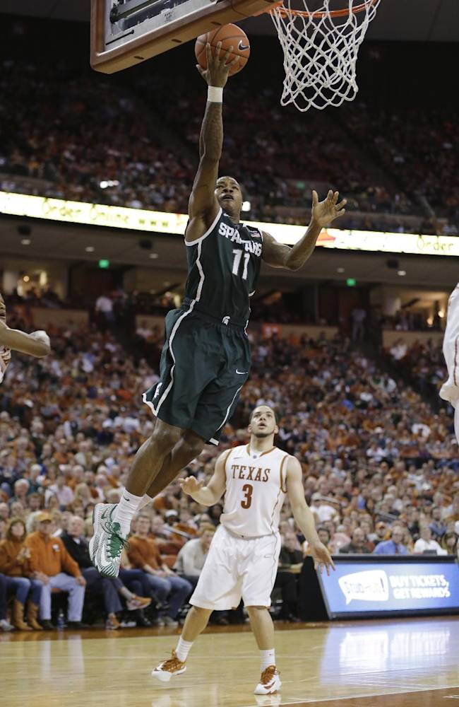 Michigan State's Keith Appling (11) scores as Texas' Javan Felix (3) looks on during the second half of an NCAA college basketball game, Saturday, Dec. 21, 2013, in Austin, Texas. Michigan State won 92-78