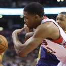Toronto Raptors' Rudy Gay battles for the ball with New Orleans Hornets' Eric Gordon, obscured, during the first half of their NBA basketball game, Sunday, Feb. 10, 2013, in Toronto. (AP Photo/The Canadian Press, Chris Young)