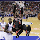 Chicago Bulls' Taj Gibson (22) hangs on the rim after dunking the ball against Philadelphia 76ers' Jarvis Varnado (40) and Byron Mullens (30) during the first half of an NBA basketball game, Wednesday, March 19, 2014, in Philadelphia The Associated Press