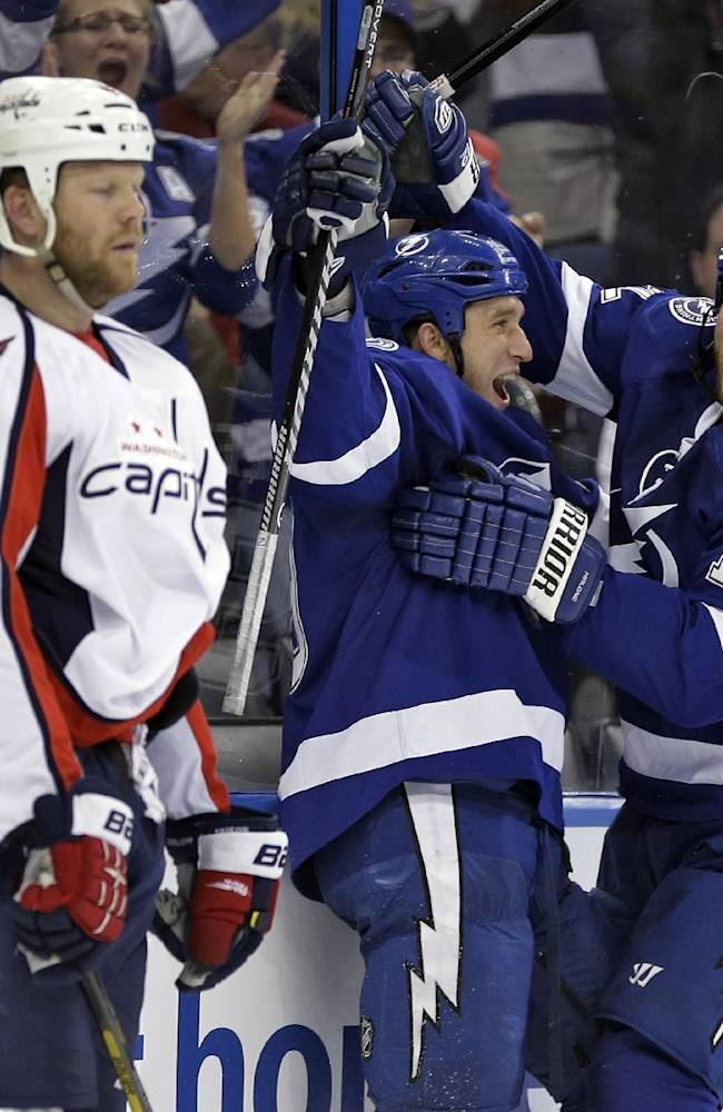 Tampa Bay Lightning right wing B.J. Crombeen, center, celebrates with teammate Ryan Malone, right, after scoring past the Washington Capitals, including defenseman John Erskine, left, during the second period of an NHL hockey game Thursday, Jan. 9, 2014, in Tampa, Fla