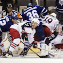 Columbus Blue Jackets goaltender Sergei Bobrovsky, right, watches as James Wisniewski, center, scrambles the puck away from Toronto Maple Leafs Tyler Bozak, left, during the first period of an NHL hockey game in Toronto on Monday, March 3, 2014 The Associ