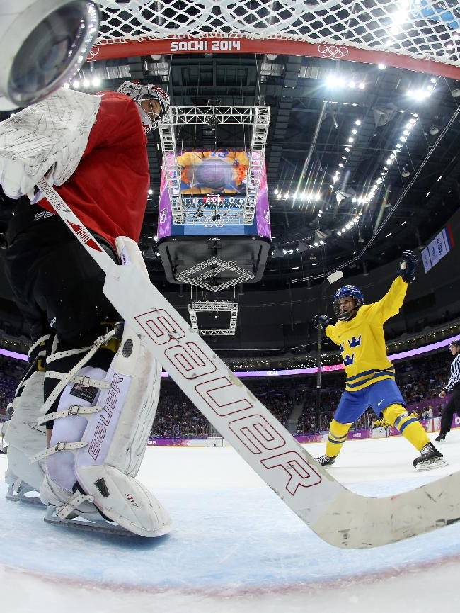 Goalkeeper Florence Schelling of Switzerland takes the puck out of the net after Michelle Lowenhielm of Sweden, not shown, during the women's bronze medal ice hockey game at the 2014 Winter Olympics, Thursday, Feb. 20, 2014, in Sochi, Russia