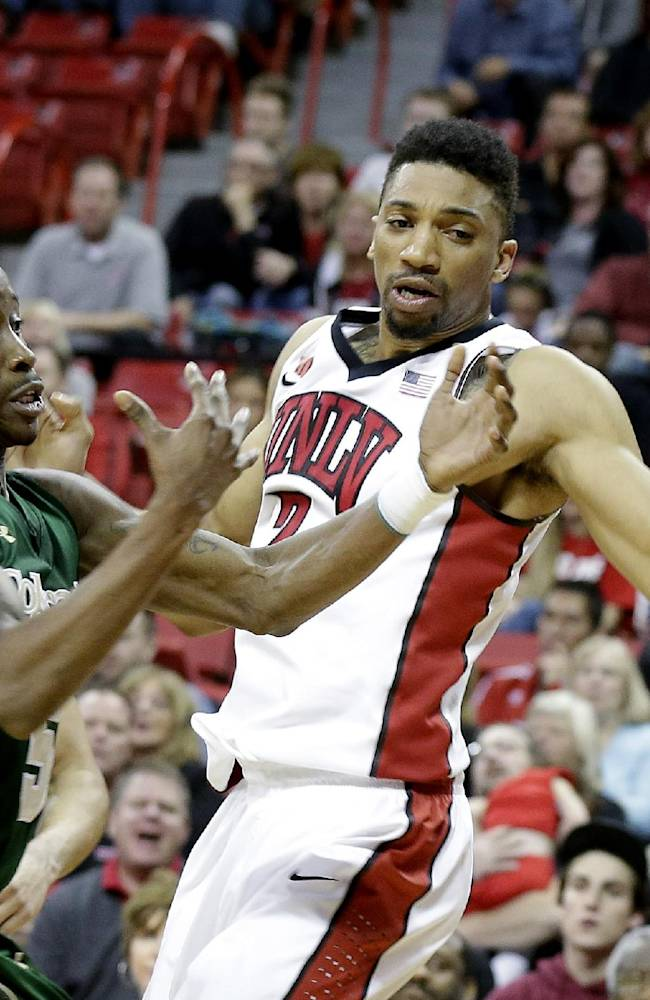 Colorado State's Jon Octeus, left, and UNLV's Khem Birch, of Canada, go after a loose ball during the second half of an NCAA college basketball game on Wednesday, Feb. 26, 2014, in Las Vegas. UNLV defeated Colorado State 78-70