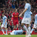 Liverpool's Jordan Henderson, center, is sent off by referee Mark Clattenburg, right, after a foul on Manchester City's Samir Nasri, bottom, during their English Premier League soccer match at Anfield Stadium, Liverpool, England, Sunday April 13, 2014