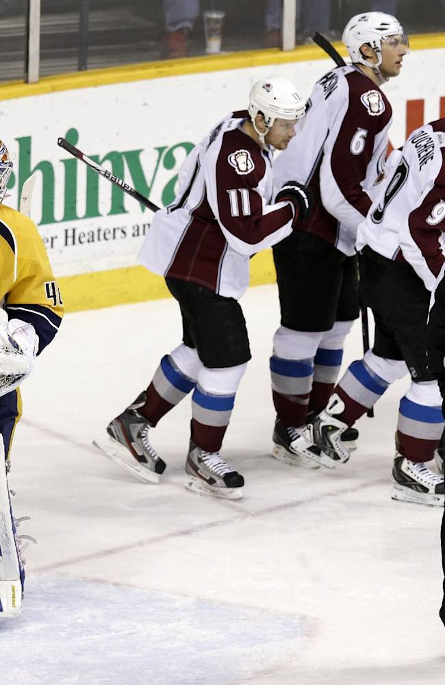Nashville Predators goalie Devan Dubnyk (40) waits by the net as Colorado Avalanche players celebrate a goal by Matt Duchene (9) in the third period of an NHL hockey game Saturday, Jan. 18, 2014, in Nashville, Tenn. The Avalanche won 5-4