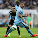 Newcastle United's Remy Cabella, left, vies for the ball with Manchester City's Aleksandar Kolarov, front, and Yaya Toure, back, during their English Premier League soccer match at St James' Park, Newcastle, England, Sunday, Aug. 17, 2014