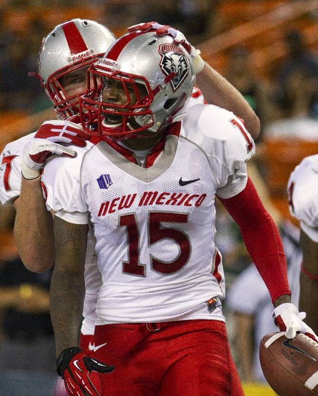 New Mexico tight end Lucas Reed (97) congratulates wide receiver SaQwan Edwards (15) after Edwards scored a touchdown against Hawaii in the first quarter of an NCAA college football game Saturday, Oct. 13, 2012, in Honolulu