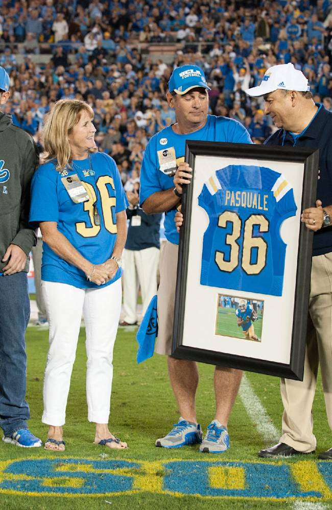 Pasquale's parents and brother joined Mora and athletic director Dan Guerrero for an on-field ceremony in honor of late UCLA receiver Nick Pasquale after the first quarter Saturday Sept. 21, 2013 in Pasadena, Calif. They stood next to Pasquale's name and No. 36, painted on the Rose Bowl turf near the spot where Pasquale lined up for his first play with the Bruins in last month's win over Nevada.  Left to right: Head Coach Jim Mora Jr., brother A.J Pasquale, mother Laurie Pasquale, father Nick Pasquale and UCLA Athletic Director Dan Guerrero