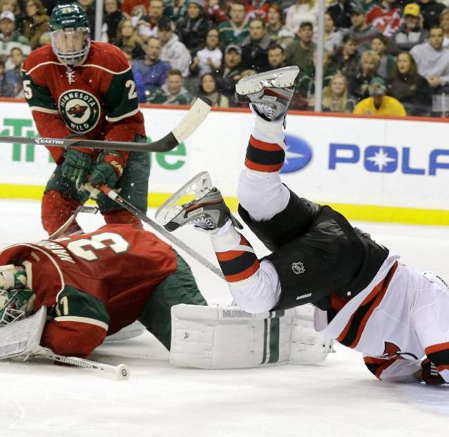 New Jersey Devils right wing Stephen Gionta, right, sails over Minnesota Wild goalie Josh Harding, center, as Harding covers the puck after stopping a shot by Gionta during the second period of an NHL hockey game in St. Paul, Minn., Sunday, Nov. 3, 2013