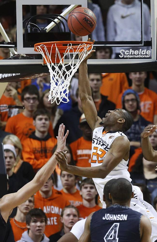 Oklahoma State wing Markel Brown (22) shoots in front of South Carolina forward Mindaugas Kacinas (25), guard Tyrone Johnson (4) and forward Demetrius Henry (21) in the first half on an NCAA college basketball game in Stillwater, Okla., Friday, Dec. 6, 2013