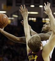 Iowa guard Devyn Marble, top, drives to the basket over Minnesota center Elliott Eliason during the second half of an NCAA college basketball game on Sunday, Jan. 19, 2014, in Iowa City, Iowa. Iowa won 94-73. (AP Photo/Charlie Neibergall)