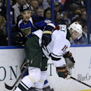 St. Louis Blues' Chris Stewart, left, and Minnesota Wild's Dany Heatley get tangled up along the boards while chasing a loose puck during the first period of an NHL hockey game Monday, Nov. 25, 2013, in St. Louis The Associated Press