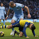 Manchester City's Pablo Zabaleta, left, attempts to gets the ball from Arsenal's Alexis Sanchez during the English Premier League soccer match between Manchester City and Arsenal at the Etihad Stadium, Manchester, England, Sunday Jan. 18, 2015