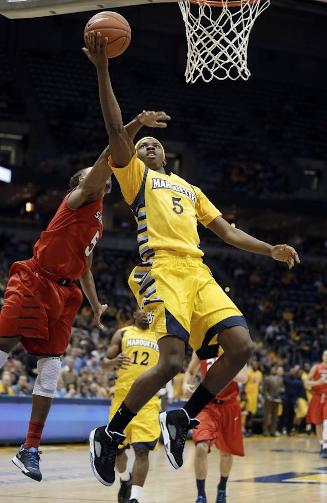 Marquette's JaJuan Johnson, right, shoots past Samford's Russell Wilson during the first half of an NCAA college basketball game Saturday, Dec. 28, 2013, in Milwaukee