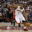 Toronto Raptors' Kyle Lowry, right, is guarded by Miami Heat's Norris Cole during the second half of an NBA basketball game in Toronto, Friday, Nov. 29, 2013 The Associated Press
