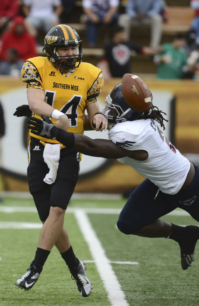 In this Nov. 16, 2013, file photo, Southern Mississippi quarterback Nick Mullens (14) throws the ball away before Florida Atlantic defensive lineman Brandin Bryant (2) tackles him in the fourth quarter of an NCAA college football game in Hattiesburg, Miss Bryant grew up hearing about the football exploits of his grandfather Charles Bryant at Nebraska, and he dreamed of the day he, too, would play at Lincoln's Memorial Stadium