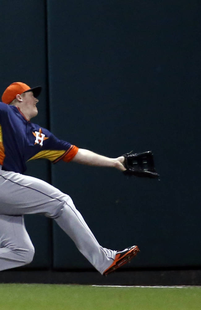 Houston Astros left fielder Marc Krauss can't catch a foul ball hit by Atlanta Braves' Chris Johnson during the third inning of a spring training baseball game, Friday, Feb. 28, 2014, in Kissimmee, Fla. The Astros won 7-5