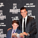 In this photo provided by the Las Vegas News Bureau, Will Lucas, left, and Patrice Bergeron of the Boston Bruins pose with the Frank J. Selke Trophy for best defensive forward at the 2014 NHL Awards at Wynn Las Vegas. Tuesday, June 24, 2014 The Associated