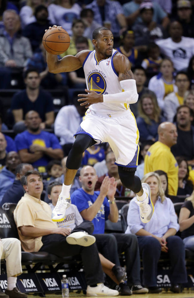 Golden State Warriors' Andre Iguodala saves the ball from going out of bounds against the Sacramento Kings during the second half of an NBA preseason basketball game Monday, Oct. 7, 2013, in Oakland, Calif