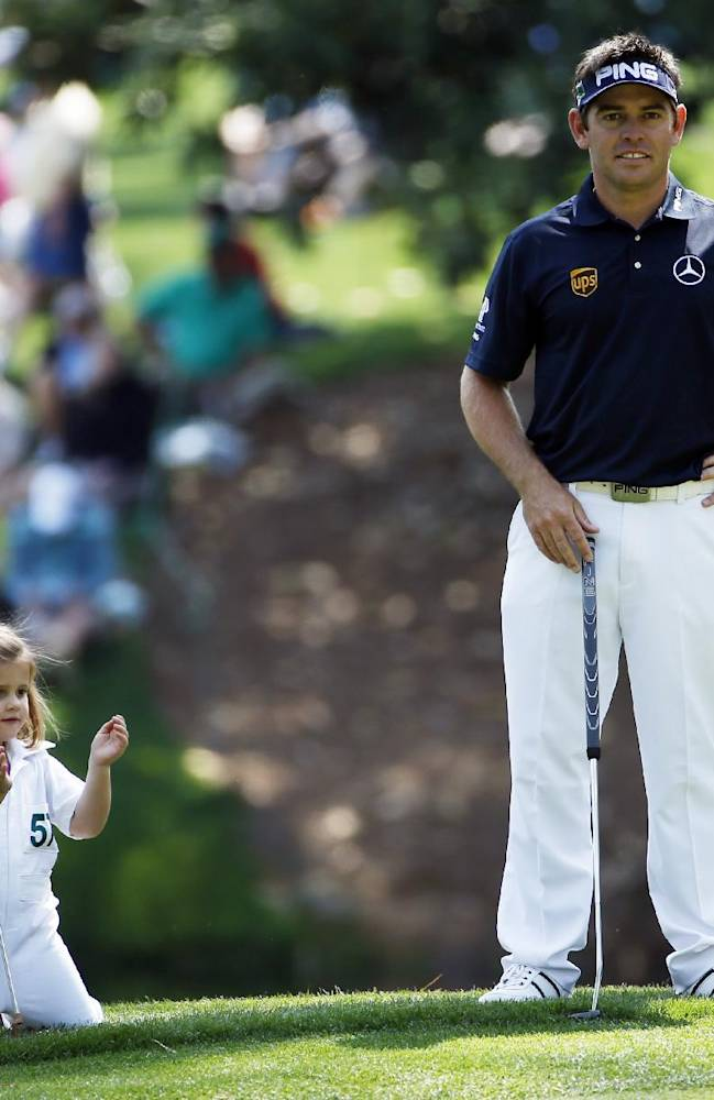 Louis Oosthuizen, of South Africa, waits to putt with his daughter Jana during the par three competition at the Masters golf tournament Wednesday, April 9, 2014, in Augusta, Ga