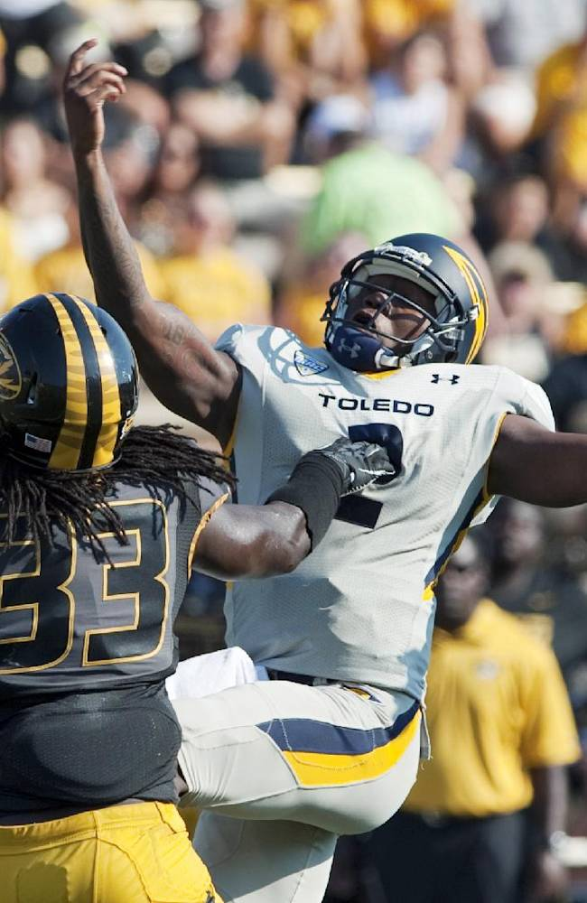 In this Sept. 7, 2013, file photo, Missouri's Markus Golden, left, reaches to intercept the ball that slipped out of Toledo quarterback Terrance Owens' hand, right, before returning it for a touchdwon during the third quarter of an NCAA college football in Columbia, Mo. Golden's 70-yard interception return against Toledo was one of Missouri's six picks this year, just one shy of its total from all of last season. The defense will get its toughest test so far against a high-octane Indiana offense, one it will face without suspended captain Andrew Wilson for the first half