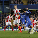 Chelsea's Mohamed Salah, center, is tackled by Stoke City's Andy Wilkinson which resulted in a penalty during their English Premier League soccer match at Stamford Bridge, London, Saturday, April 5, 2014