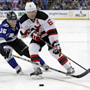 Tampa Bay Lightning defenseman Matthew Carle (25) and New Jersey Devils defenseman Andy Greene (6) reach for the puck during the third period of an NHL hockey game Saturday, March 15, 2014, in Tampa, Fla. The Lightning won 3-0 The Associated Press