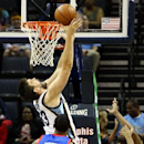Memphis Grizzlies center Marc Gasol (33) lays the ball in the basket while being defended by Philadelphia 76ers forward Thaddeus Young (21) and guard James Anderson (9) in the first half of an NBA basketball game on Friday, April 11, 2014, in Memphis, Ten