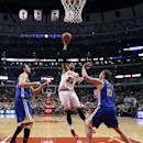 Chicago Bulls forward Taj Gibson (22) shoots between Golden State Warriors center Andrew Bogut, left, and David Lee (10) during the first half of an NBA basketball game, Wednesday, Feb. 26, 2014, in Chicago The Associated Press