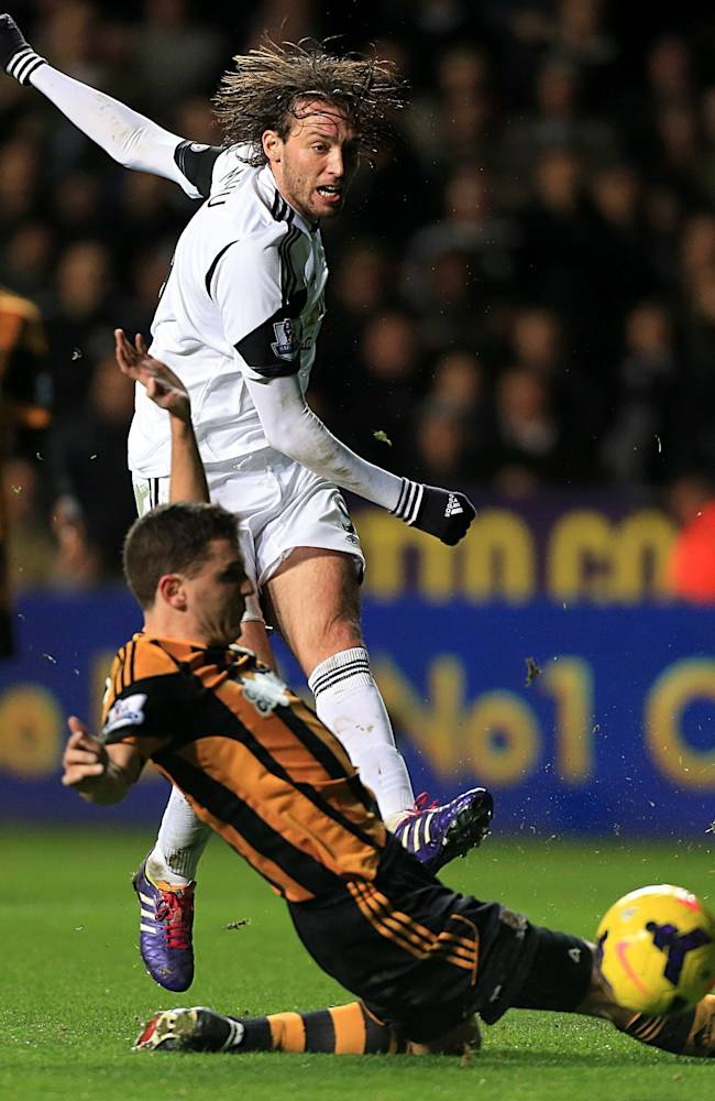 Hull City's Alex Bruce, foreground slides in on Swansea City's Miguel Michu who takes a shot at the goal, during their  English Premier League soccer match against Hull City,  at the Liberty Stadium, Swansea, Wales,  Monday Dec. 9, 2013