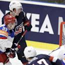 Torey Krug of USA, left, shoots to score past Russia's goalkeeper Sergei Bobrovski, second from right, during the Hockey World Championships Group B match in Ostrava, Czech Republic, Monday, May 4, 2015. (AP Photo/Sergei Grits)
