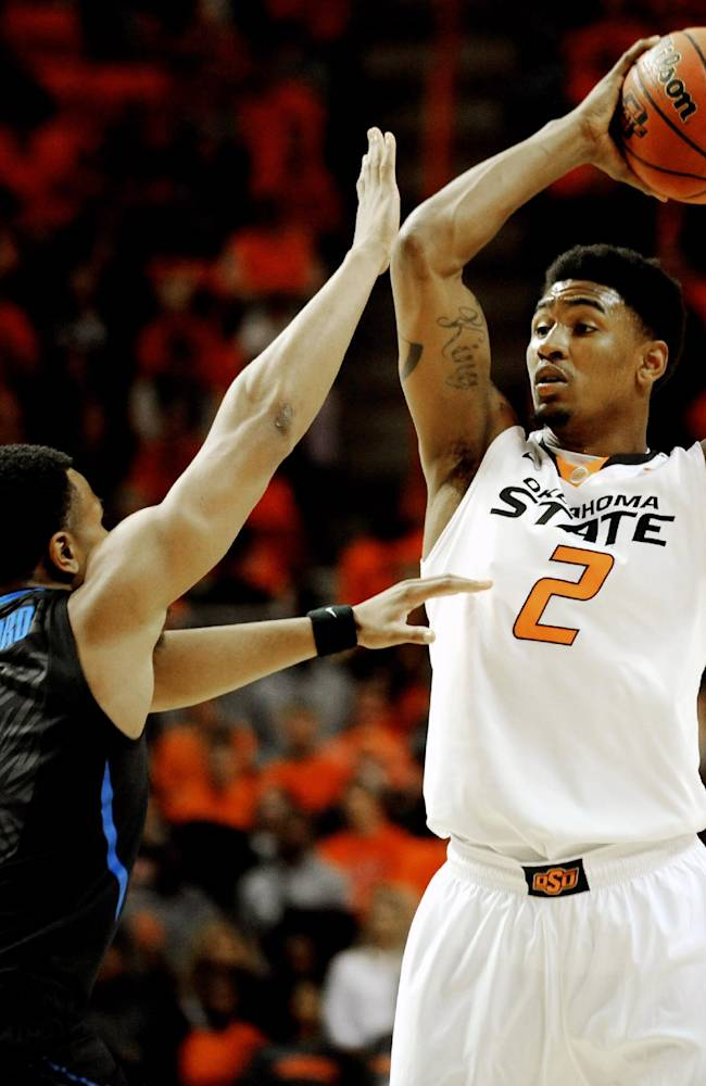 Oklahoma State wing Le'Bryan Nash looks over Memphis guard Chris Crawford during the first half of an NCAA college basketball game in Stillwater, Okla., Tuesday, Nov. 19, 2013