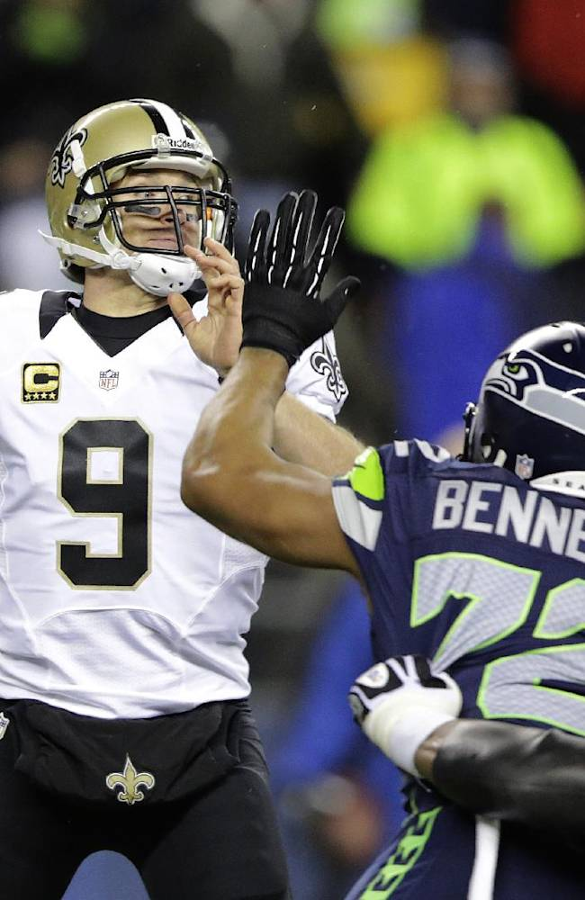 In this Dec. 2, 2013, file photo, New Orleans Saints quarterback Drew Brees (9) passes under pressure from Seattle Seahawks defensive end Michael Bennett (72) during an NFL football game in Seattle. NFL free agency begins Tuesday, March 11, 2014, with each team having another $10 million or so to spend thanks to the increased salary cap. Such standouts as receivers Eric Decker and Julian Edelman, defensive end Michael Bennett and cornerback Alterraun Verner figure to draw quick attention