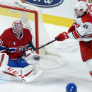 Montreal Canadiens goalie Carey Price (31) makes a save as Carolina Hurricanes center Victor Rask (49) swings at the loose puck during the first period of an NHL hockey game Tuesday, Dec. 16, 2014, in Montreal The Associated Press