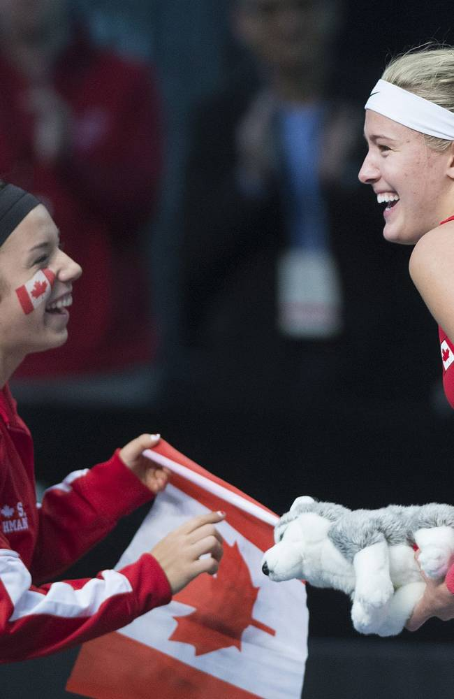 Canada's Eugenie Bouchard celebrates with teammate Sharon Fichman, left, after defeating Vesna Dolonc, of Serbia, during a Federation Cup tennis match in Montreal, Sunday, Feb. 9, 2014