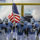 In this Sept. 3, 2011 file photo, North Carolina takes the field against James Madison in an NCAA college football game in Chapel Hill, N.C. The NCAA infractions committee has hit North Carolina's football program with a one-year postseason ban, a reducti